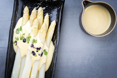 Traditional boiled white asparagus with sauce hollandaise and herbs as top view on a plate with copy space right
