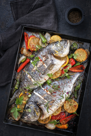Two fresh barbecue gilthead seabreams with vegetable and fruits as top view in an old metal sheet Stock Photo