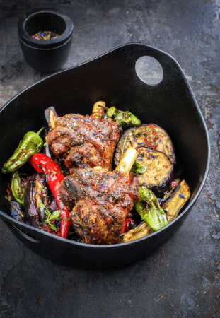 Traditional barbecue leg of lamb with eggplant and chili as top view in a modern style Japanese cast-iron roasting dish Stock Photo