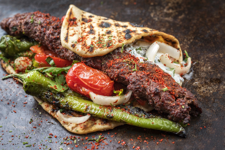 Traditional Adana kebap on a skewer with tomato and yogurt as closeup on a flatbread Banque d'images