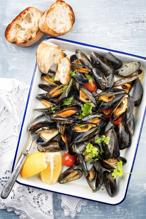 Traditional barbecue Italian blue mussel with baguette and tomatoes in white wine as top view on a tray Stock fotó - 121312165