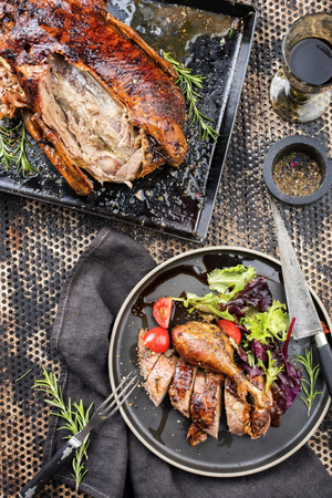 Traditional roasted Christmas duck with lettuce and tomatoes as top view on a plate Stock Photo