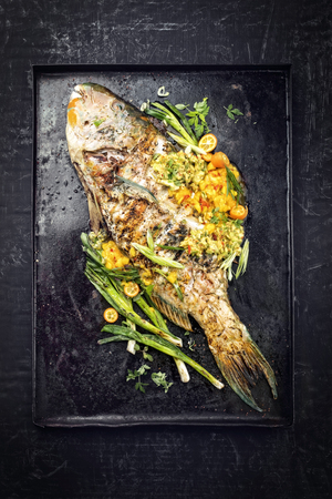 Traditional BBQ parrotfish with mango salsa as top view on a black board