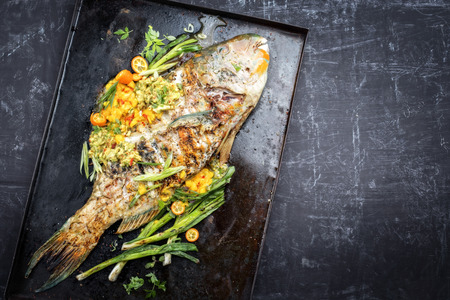 Traditional BBQ parrotfish with mango salsa as top view on a black board copy space right Stock Photo
