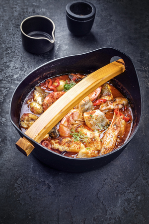 Traditional American cajun fish stew with prawns, mussels and fish as top view in a modern design Japanese cast-iron roasting dish