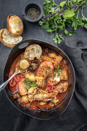 Traditional French Corsican fish stew with prawns, mussels and fish as top view in a modern design Japanese cast-iron roasting dish Stock Photo
