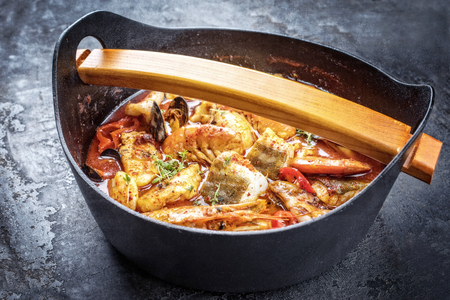 Traditional Italian American cioppino fish stew with prawns, mussels and fish as top view in a modern design Japanese cast-iron roasting dish
