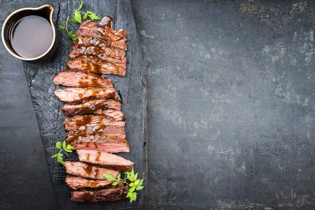Bistecca di fianco invecchiata a secco con barbecue tradizionale americana affettata con salsa piccante e peperoncino come vista dall'alto su una vecchia tavola carbonizzata con spazio copia a destra Archivio Fotografico