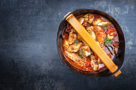 Traditional French bouillabaisse with prawns, mussels and fish as top view in a modern design Japanese cast-iron roasting dish
