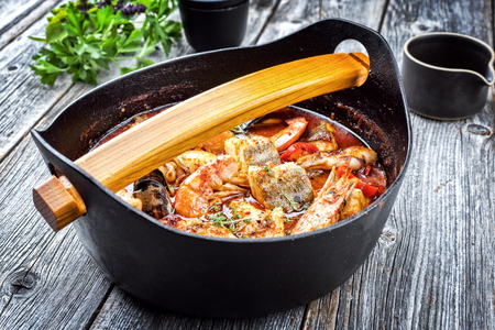Traditional Catalan sarsuela seafood stew with prawns, mussels and fish as top view in a modern design Japanese cast-iron roasting dish