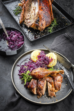 Traditional roasted Christmas duck with potato dumplings and blue kraut as top view on a plate