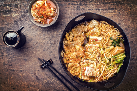 Traditional Korean kimchi jjigae with grilled pork belly and ramen as top view in a modern design Japanese cast-iron roasting dish - vintage Stock Photo