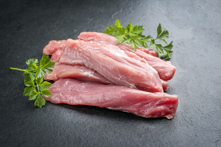 Raw suckling pig fillet offered on a black slate slab as closeup 写真素材