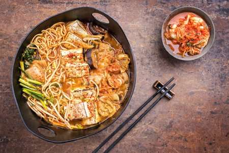 Traditional Korean kimchi jjigae with grilled pork belly and ramen as top view in a modern design Japanese cast-iron roasting dish Stockfoto - 121312366
