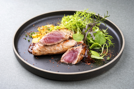 Fried suckling pig fillet with potatoes and lettuce offered as closeup in a modern design plate with spicy sauce