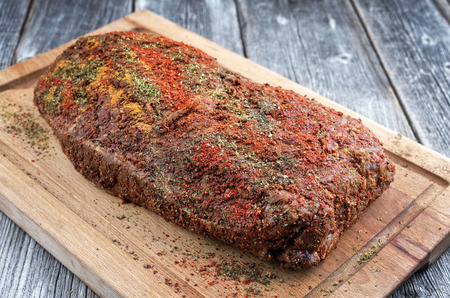 Traditional raw pulled pork piece of Bosten butt with spicy rub as closeup on a wooden cutting board