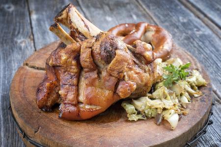 Traditionelles bayerisches Schweinshaxe mit Krautsalat und Preztel als Nahaufnahme auf einem Holzbrett Standard-Bild