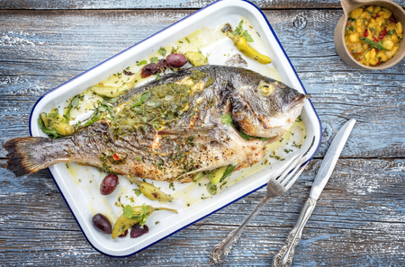 Fresh barbecue gilthead seabream with mango chutney and pesto as top view in a white skillet Stock Photo