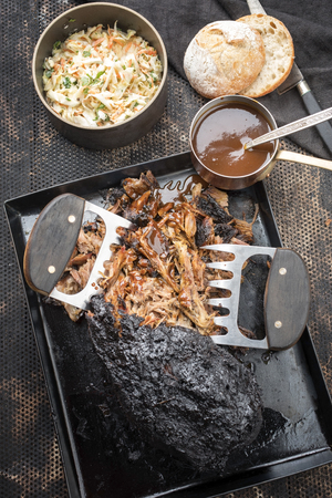 Traditional barbecue pulled pork piece of Bosten butt torn to bits with coleslaw and burger as top view on a board
