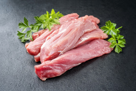 Raw suckling pig fillet offered on a black slate slab as closeup Stock Photo
