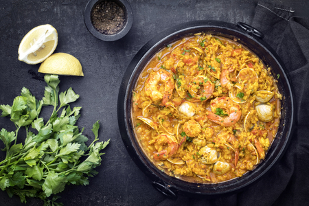 Traditional Portuguese arroz caldoso con almejas with shrimps and calm as top view in a cast-iron pot Stock Photo