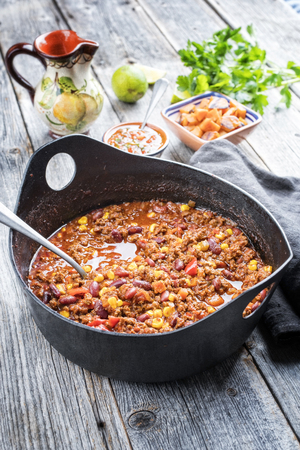 Traditional slow cooked Mexican chili con cane with mincemeat, beans and corn as top view in a modern design cast-iron roasting dish Stock Photo
