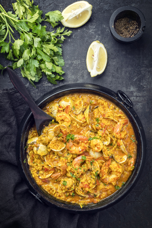 Traditional Portuguese arroz caldoso con almejas with shrimps and calm as top view in a cast-iron pot 免版税图像