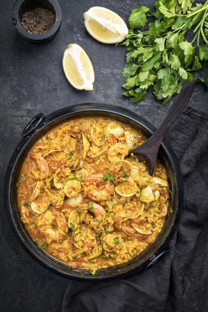 Traditional Portuguese arroz caldoso con almejas with shrimps and calm as top view in a cast-iron pot Banco de Imagens