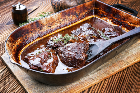 Traditional German braised veal cheeks in brown sauce with mushroom and onions as closeup in a stewpot Stockfoto