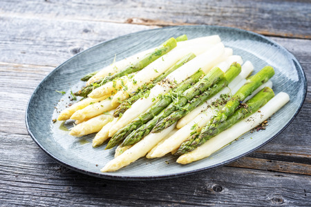 Traditional boiled white and green asparagus with butter sauce decorated with cress as closeup on a design plate on a wooden table