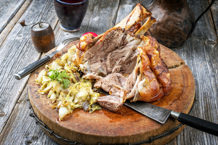 Traditional Bavarian schweinshaxe with coleslaw and preztel as closeup on a wooden cutting board