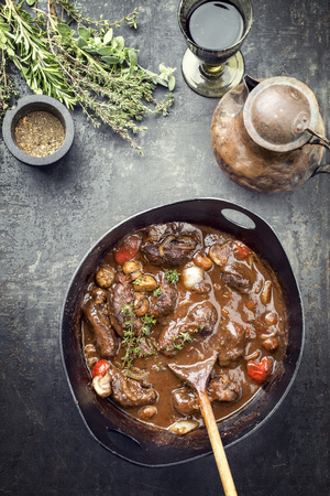 Traditional German braised pork cheeks in brown sauce with mushroom and carrots as top view in a cast-iron pot Banco de Imagens - 121312459