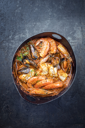 Traditional Catalan fish stew romesco de peix with prawns, mussels and fish as top view in a modern design cast-iron roasting dish with copy space Stock Photo