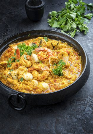 Traditional Portuguese arroz caldoso con almejas with shrimps and calm as top view in a cast-iron pot Imagens