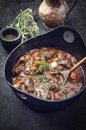 Traditional German braised pork cheeks in brown sauce with mushroom and carrots as closeup in a cast-iron pot Фото со стока