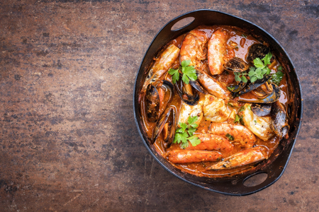 Traditional Catalan fish stew romesco de peix with prawns, mussels and fish as top view in a modern design cast-iron roasting dish with copy space left Stock Photo