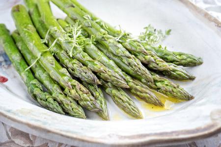Traditionele gekookte groene asperges met botersaus versierd met tuinkers als close-up op een designplaat