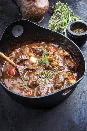 Carrilleras de cerdo estofado tradicional alemán en salsa marrón con champiñones y zanahorias como primer plano en una olla de hierro fundido