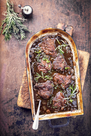 Traditional German braised veal cheeks in brown sauce with mushroom and onions as top view in a stewpot Stock Photo