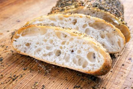 Traditional Italian ciabatta bread with herbs as closeup on a cutting board
