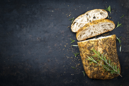 Traditional Italian ciabatta bread with herbs as top view on an old black board with copy space left