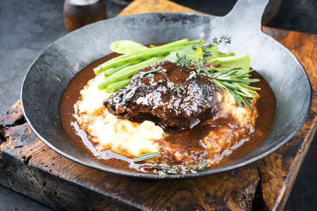 Joues de veau braisées traditionnelles allemandes en sauce brune avec purée de pommes de terre et haricots en gros plan dans une poêle en fer forgé