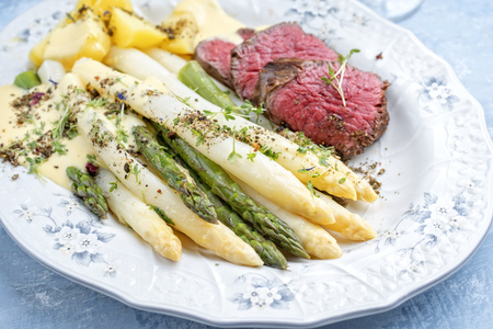 Espárragos blancos y verdes tradicionales con filete de ternera en rodajas añejo seco barbacoa y patatas fritas servido como primer plano en una placa de diseño shabby chic