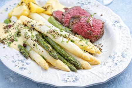 Traditioneller weißer und grüner Spargel mit gegrilltem, trocken gereiftem Rinderfilet und Bratkartoffeln, serviert als Nahaufnahme auf einem Shabby-Chic-Design-Teller