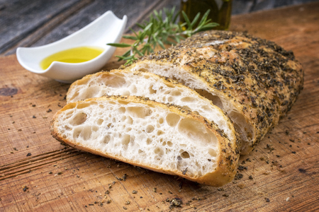 Traditional Italian ciabatta bread with herbs and olive oil as closeup on a cutting board