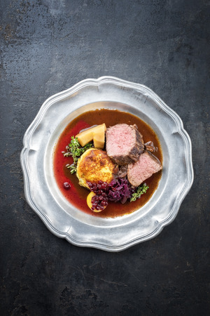 Traditional saddle of venison with fried mashed potatoes and red cabbage in game red wine sauce as top view on a pewter plate with copy space 版權商用圖片