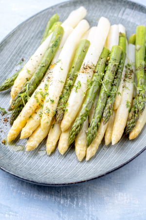 Traditional boiled white and green asparagus with butter sauce decorated with cress as closeup on a design plate on a table Фото со стока