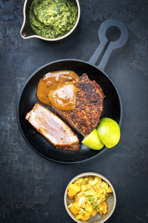 Traditional exotically blackened Cajun style tuna fish fillet with mango avocado salad, chimichurri dip and spicy BBQ sauce as top view in a modern design cast-iron pan