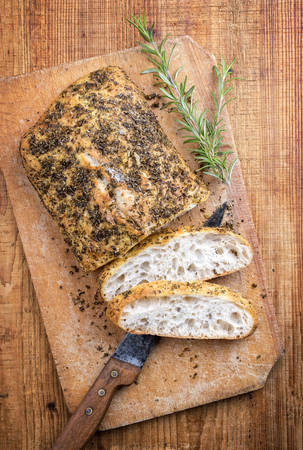Traditional Italian ciabatta bread with herbs as top view on a cutting board Stock Photo