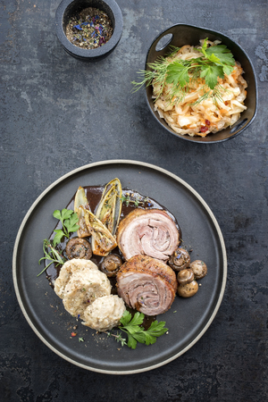 Traditional rolled boar roast with dumpling, fried vegetable and mushroom as top view on a modern design plate with game red wine sauce Stock Photo
